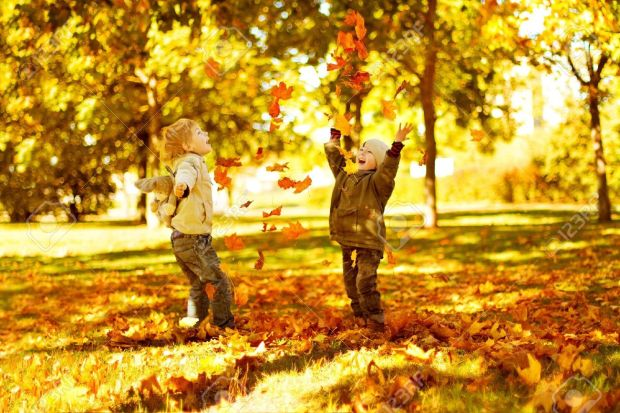 15337864-Children-playing-with-autumn-fallen-leaves-in-park-Stock-Photo