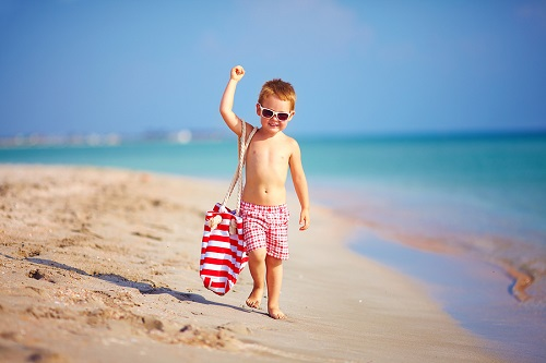 Cute Kid Boy Walking The Sea Beach